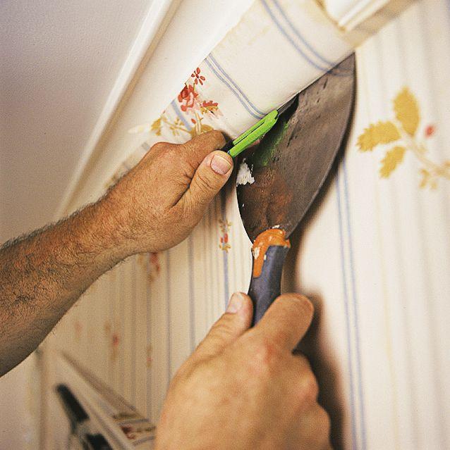 Man Trimming Wallpaper Strip At Ceiling
