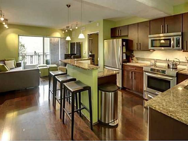 Interior of an open-plan condo kitchen/living area with some parts lime green