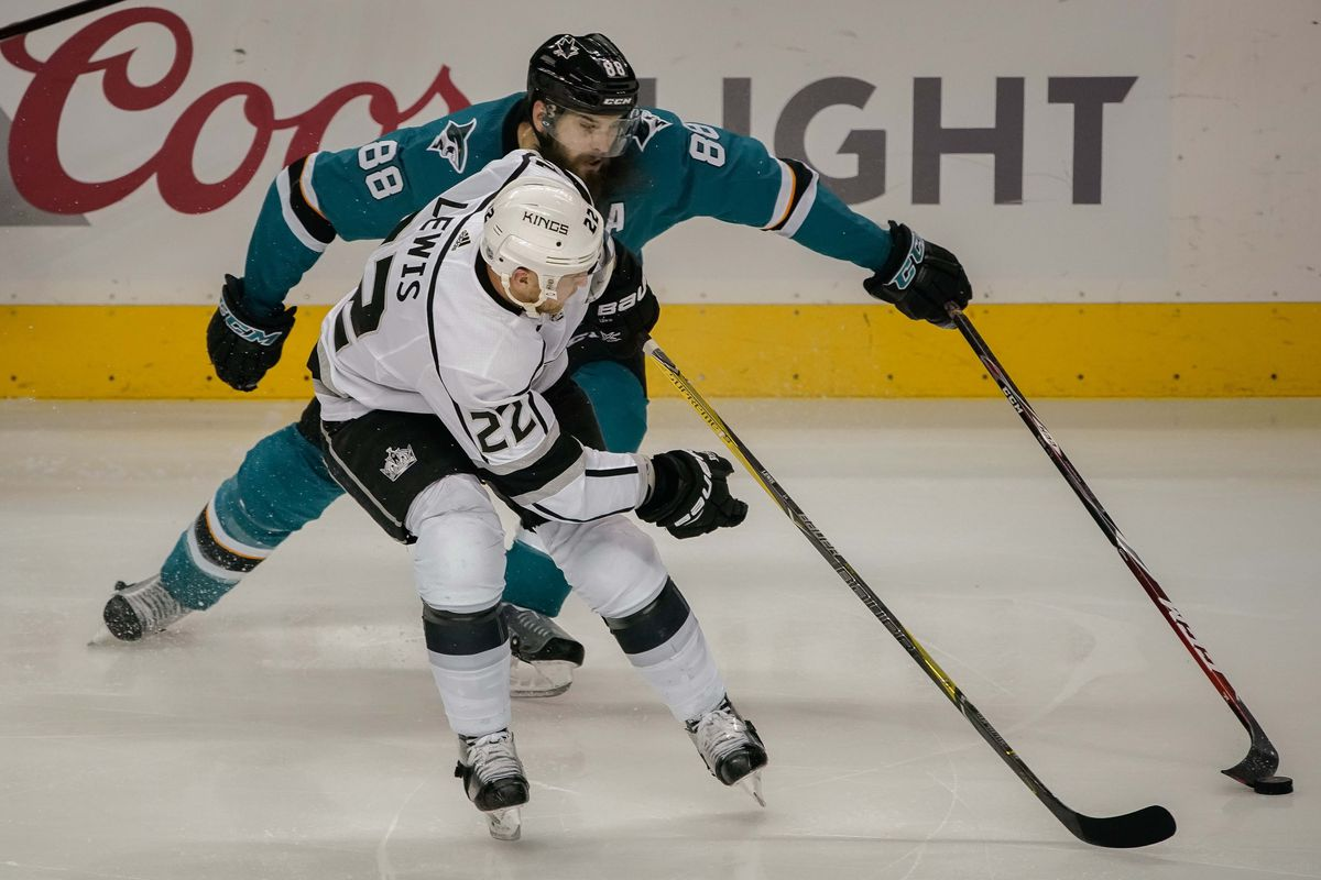Dec 23, 2017; San Jose, CA, USA; San Jose Sharks defenseman Brent Burns (88) and Los Angeles Kings center Trevor Lewis (22) fight for control of the puck during the third period at SAP Center at San Jose.