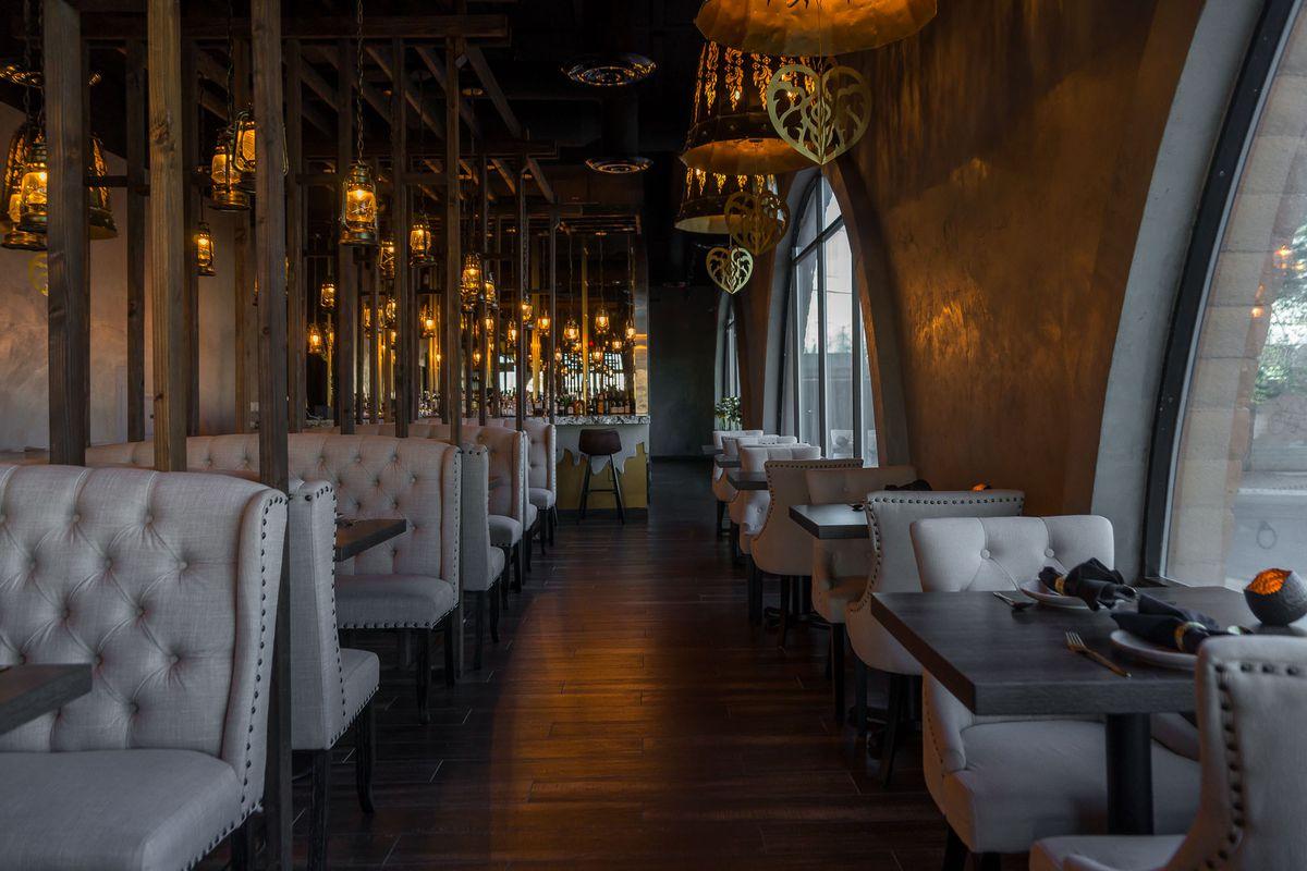 A dark restaurant with gray booths.