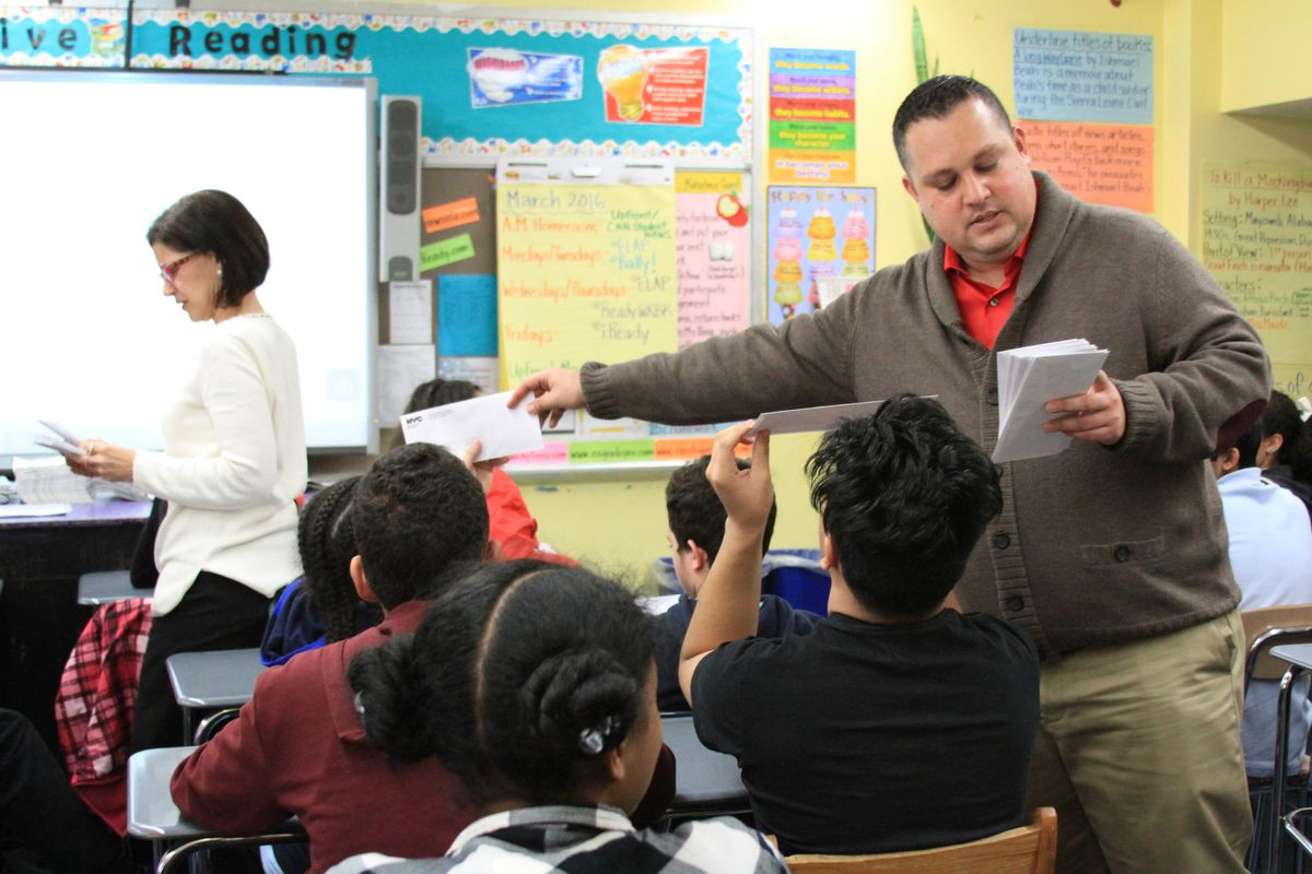 M.S. 244 Principal Eduardo Mora and guidance counselor Nancy Acosta handed out high school offer letters to eighth-graders on Friday.