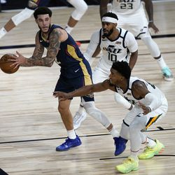 New Orleans Pelicans' Lonzo Ball, left, looks to pass as Utah Jazz's Mike Conley (10) and Donovan Mitchell, bottom right, defend during the second half of an NBA basketball game Thursday, July 30, 2020, in Lake Buena Vista, Fla. (AP Photo/Ashley Landis, Pool)