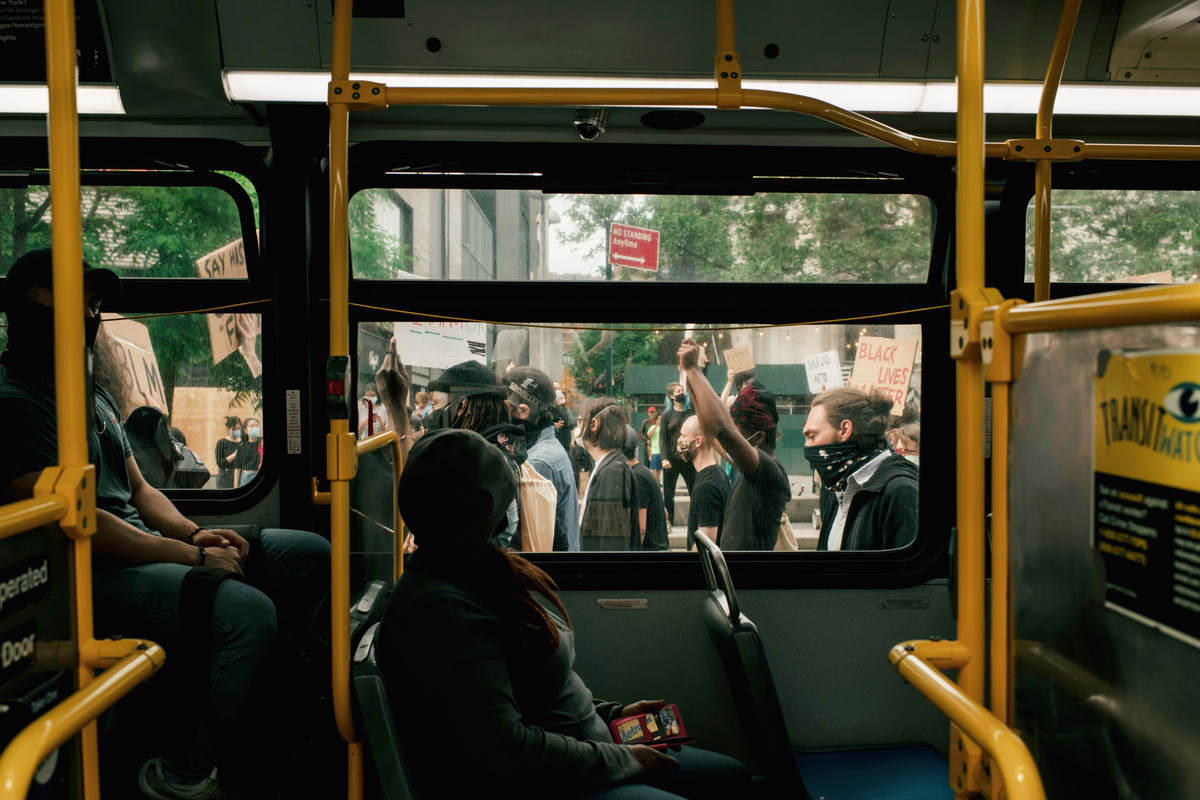 Protesters in Brooklyn, New York march past a public transit bus in the street.