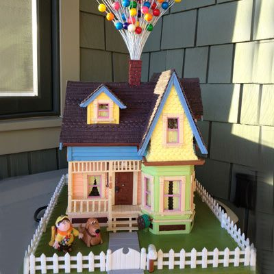 Gingerbread house replica of the home from the movie up complete with the boy and dog sitting outside in the yard.