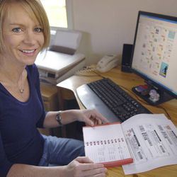 Kim Danger, a family savings expert for coupons.com, poses for a photograph with coupons available on the Internet and her personal price book at her home in Mankato, Minn., Saturday, Oct. 25, 2008.