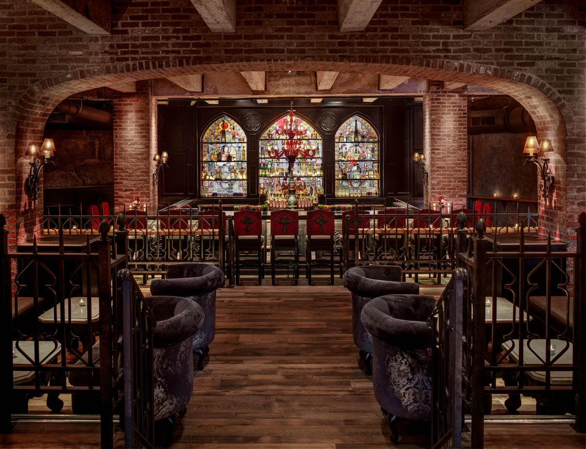 This view of a restaurant interior features a brick-lined, cavernous space. Red seats with crosses on their backs sit in front of a bar, which has three distinctive stained glass panels behind it.