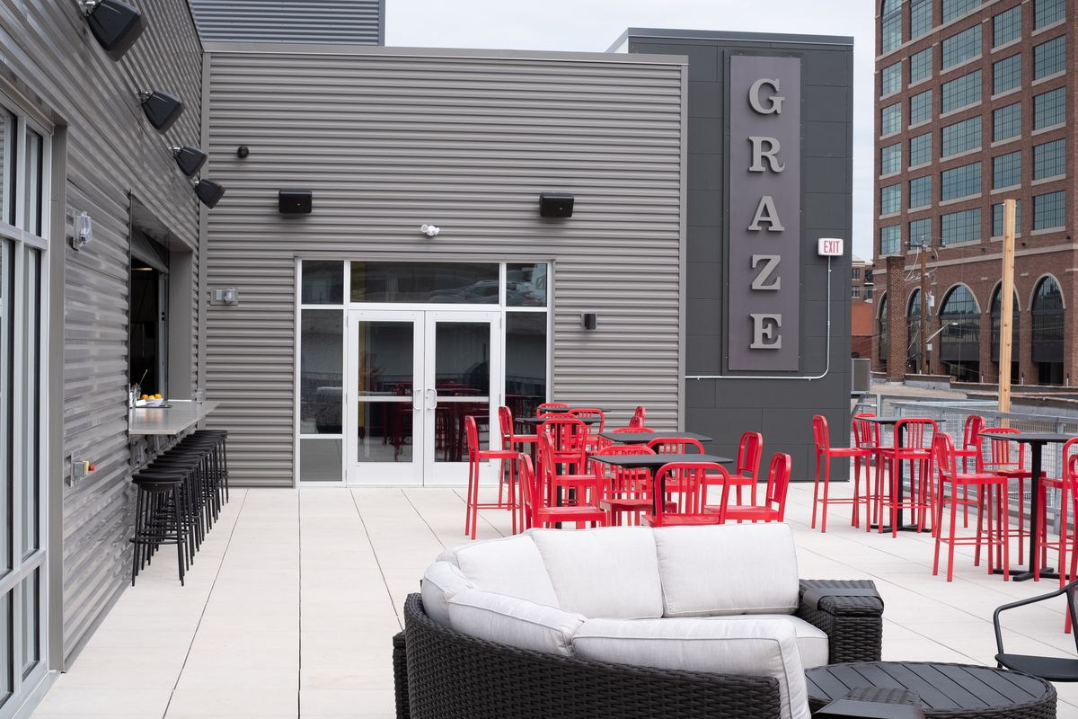 Red chairs and black tables on the rooftop patio at Graze