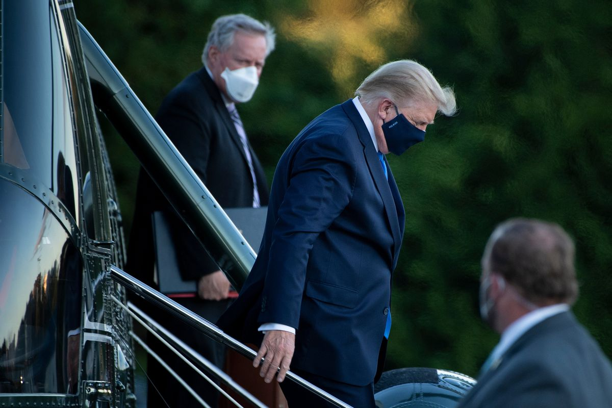 Trump, in a dark blue suit and black mask, carefully descends the helicopter's staircase, his hand on the silver railing. Behind him, chief of staff Mark Meadows looks on in a white mask.