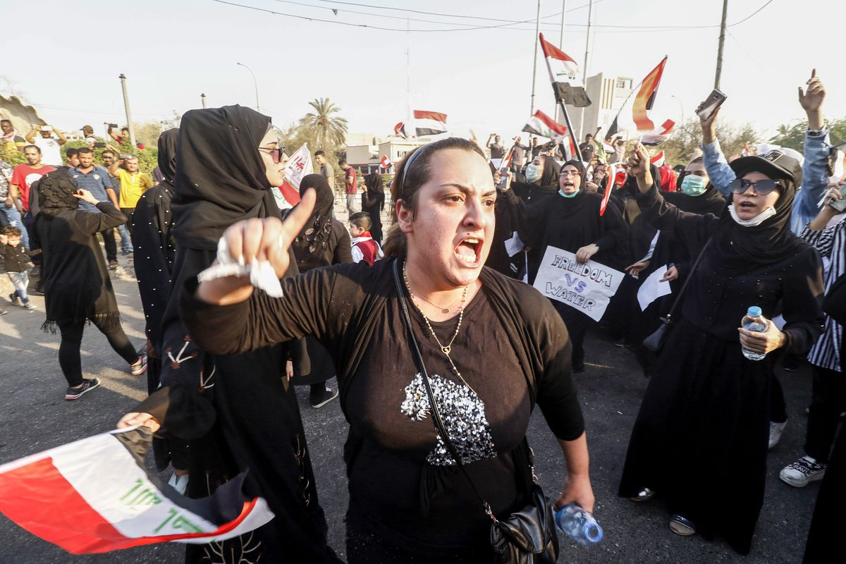 Iraqi protesters chant slogans as they gather outside the burnt-down local government headquarters in the southern city of Basra on September 7, 2018.