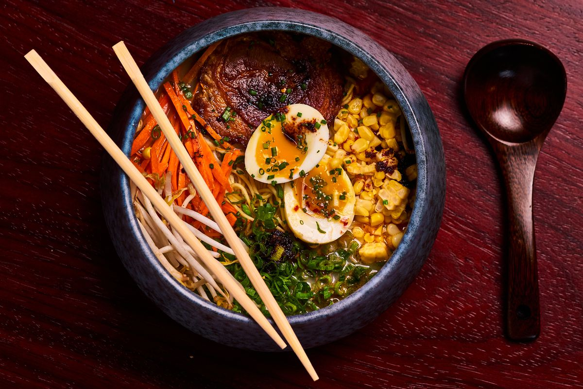 A bowl of ramen with shredded carrot, chashu pork, corn, sliced scallions, and a soft-boiled egg.