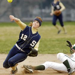 Skyline's #12 Maya Lacy tries to make a throw to first base after getting Olympus' #19 Nicole Rockwood out at second base as Skyline and Olympus play Thursday, March 29, 2012. Skyline won 7-6.