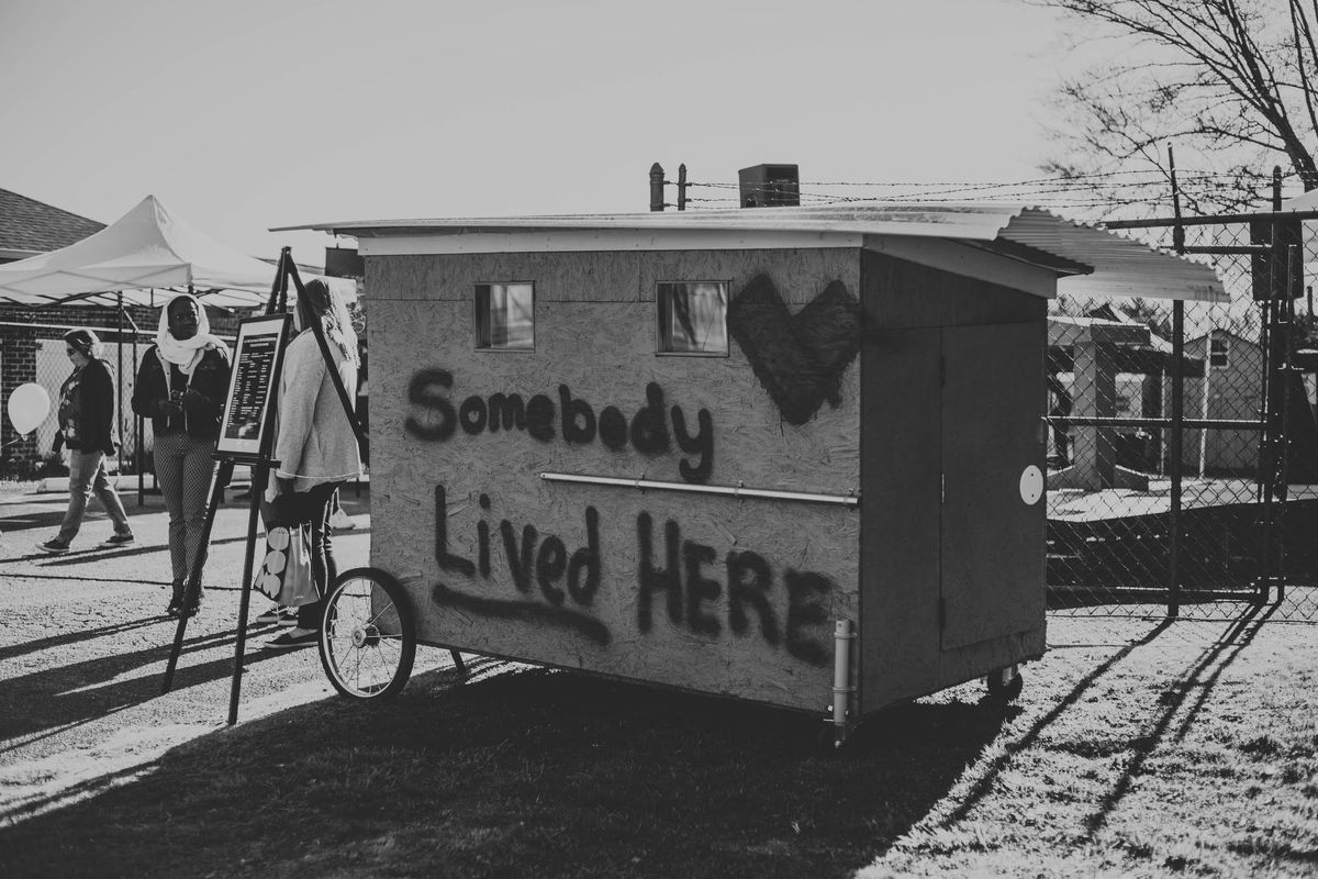 """A makeshift home built out of plywood and bicycle wheels has two small windows. It's spray painted, """"Somebody lived here."""""""