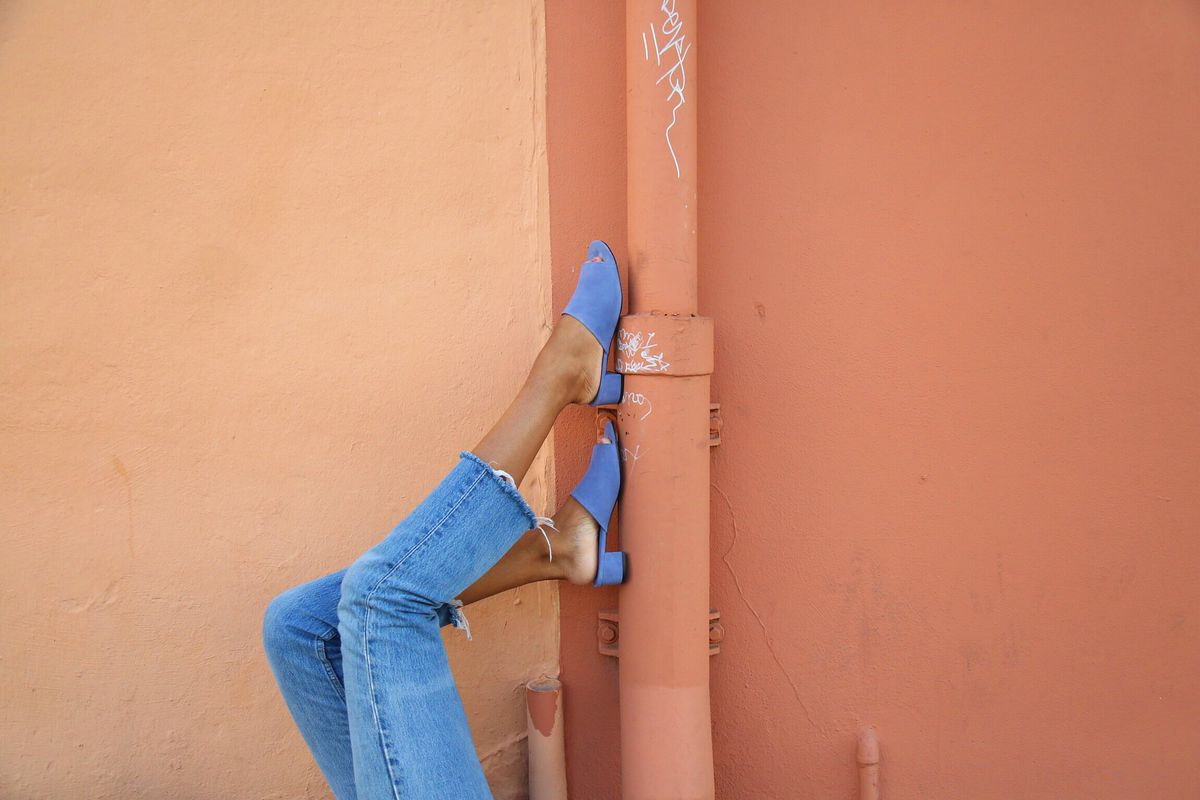 A wearing blue jeans rests her feet in blue shoes against a tan and orange painted building.