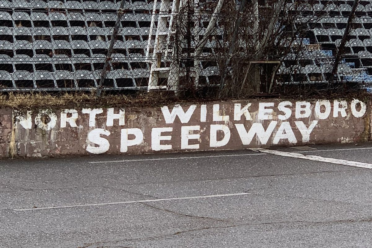 Rusted sign saying NORTH WILKESBORO SPEEDWAY beside the finish line's flag stand, overgrown with trash trees.