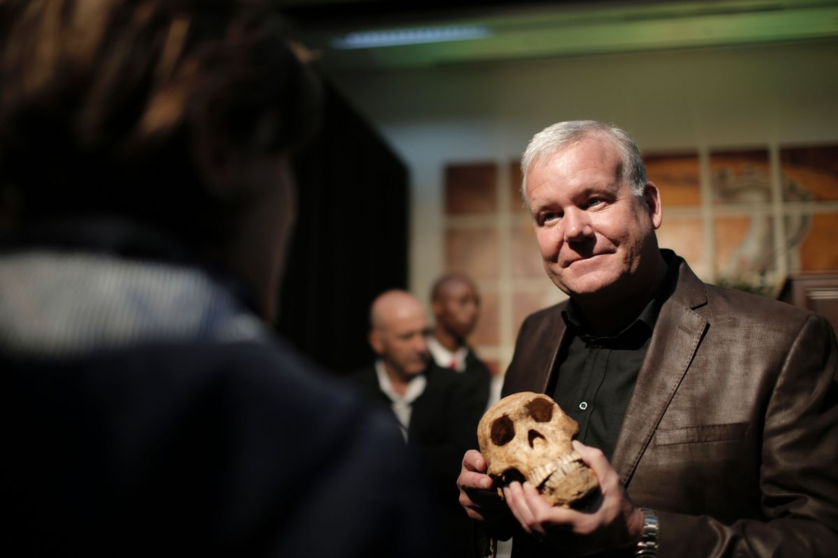 Lee Rogers Berger holds a replica of the skull of a new skeleton fossil finding.