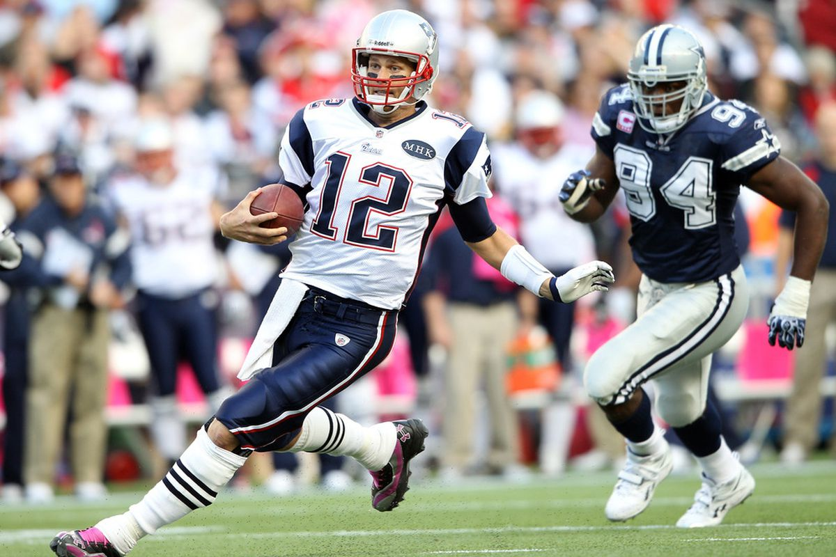 FOXBORO, MA - OCTOBER 16:   Tom Brady #12 of the New England Patriots carries the ball as  DeMarcus Ware #94 of the Dallas Cowboys defends on October 16, 2011 at Gillette Stadium in Foxboro, Massachusetts.  (Photo by Elsa/Getty Images)