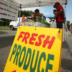 Customers buy produce during the Sugar House Farmers Market in Sugar House Park in Salt Lake City Friday, July 5, 2013.