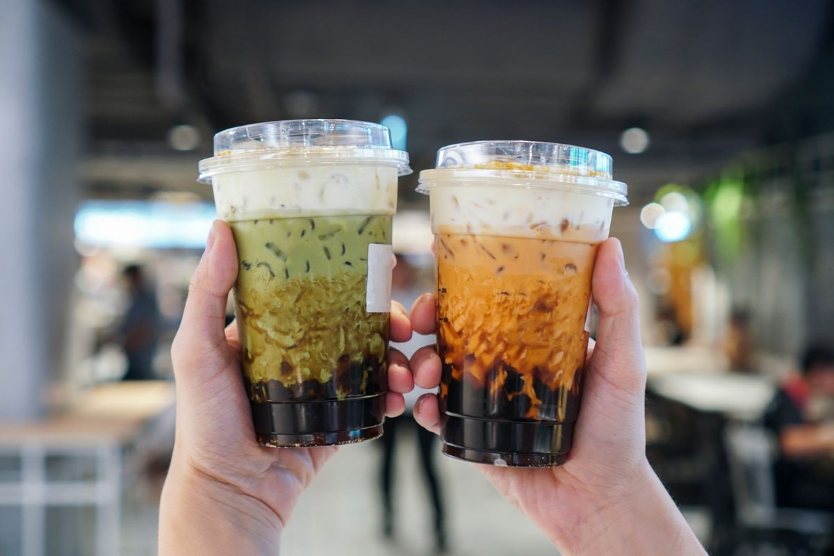 Two hands hold separate cups of bubble tea