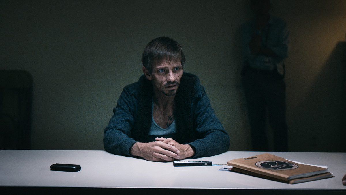 Jesse in a police interrogation room. he looks beaten and downtrodden