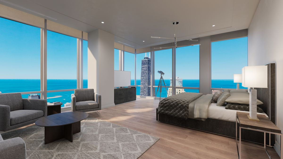 A bedroom space in a condo unit with a sitting area and wrap around views of a large body of water and a handful of very tall buildings.