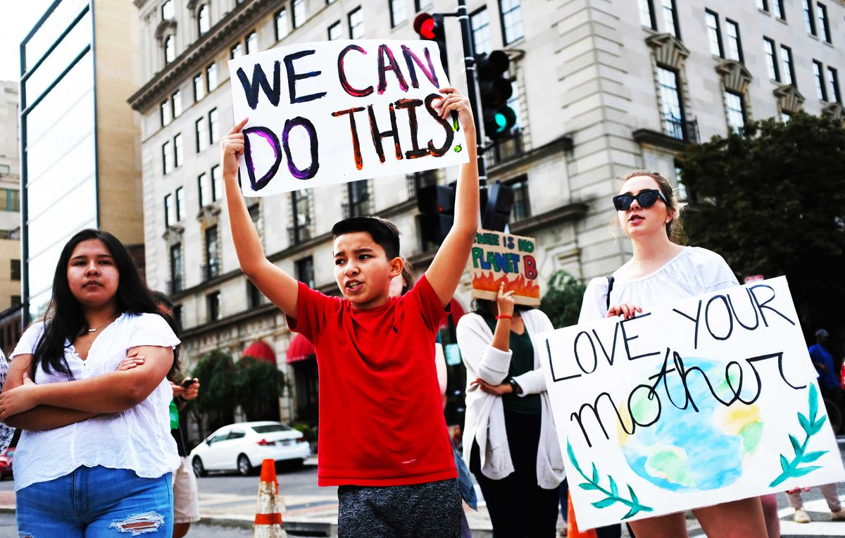 "A boy holds a protest sign that reads, ""We can do this!"" beside a woman whose sign reads, ""Love your mother"" with a picture of the Earth."