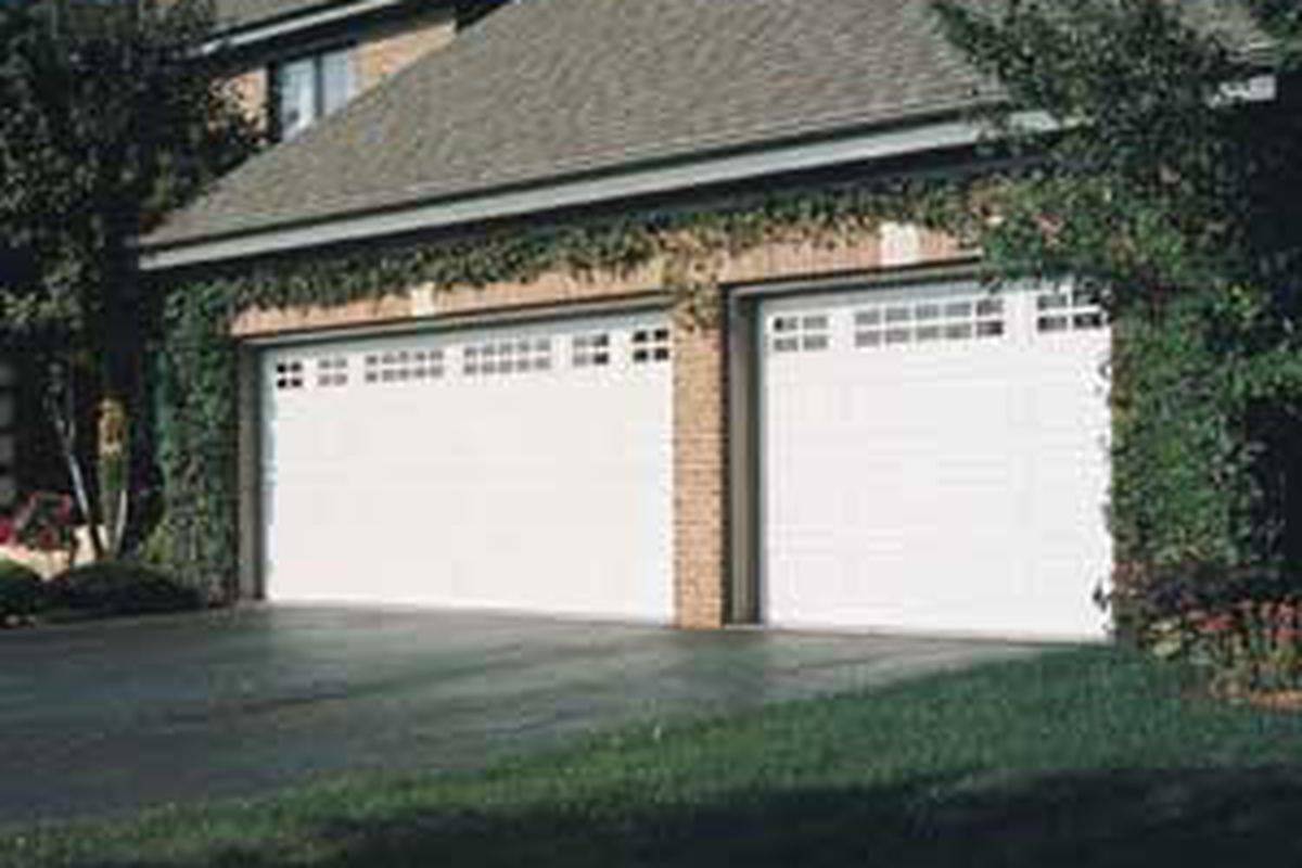 Two white garage doors on a house with a brick pattern.