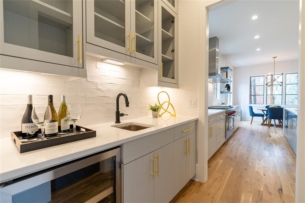 A white wet bar with brass hardware.