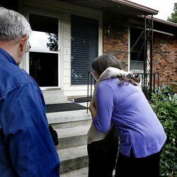 Bob and Kat, the next door neighbors of James and Jean Warhola, hug a news reporter following an interview.