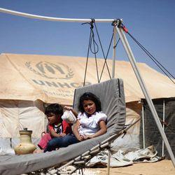 Syrian refugee children sit on a handmade swing in front of their tent, at Zaatari Refugee Camp, in Mafraq, Jordan, Sunday, Sept. 2, 2012.