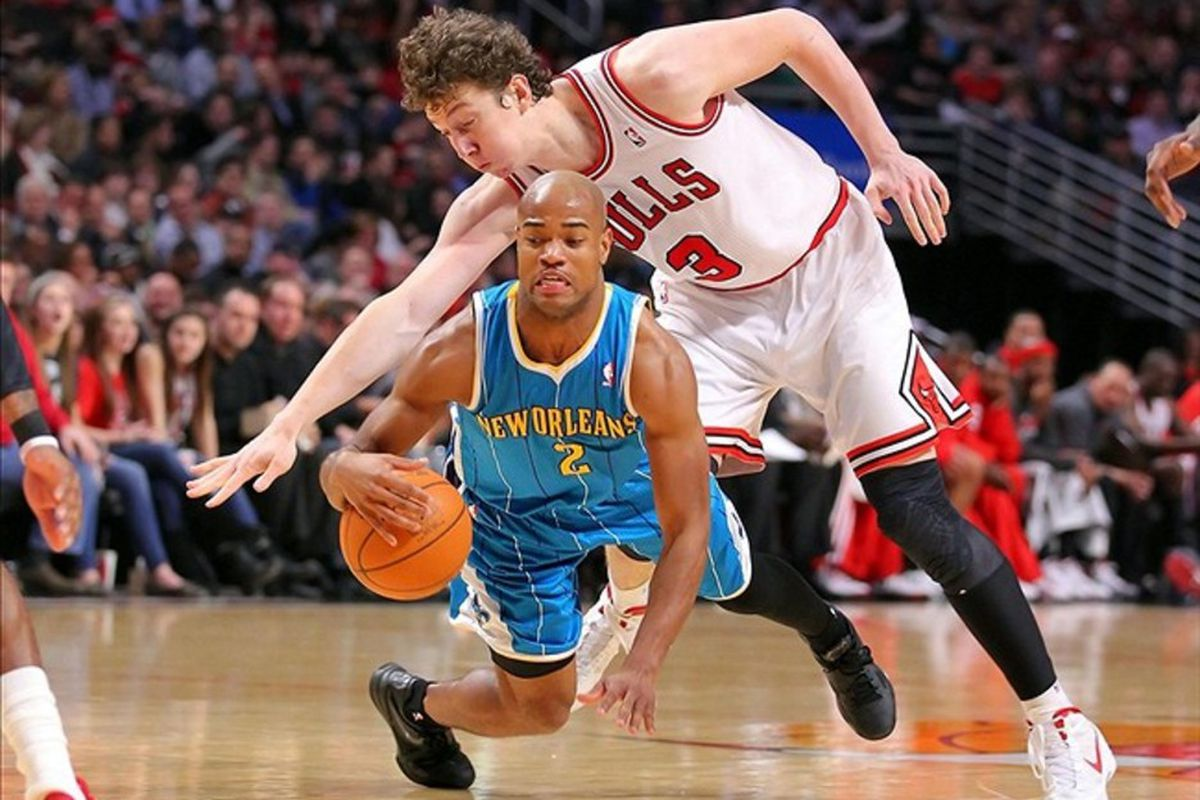 Feb 28, 2012; Chicago, IL, USA; New Orleans Hornets point guard Jarrett Jack (front) is fouled by Chicago Bulls center Omer Asik (back) during the first half at the United Center. Mandatory Credit: Dennis Wierzbicki-US PRESSWIRE