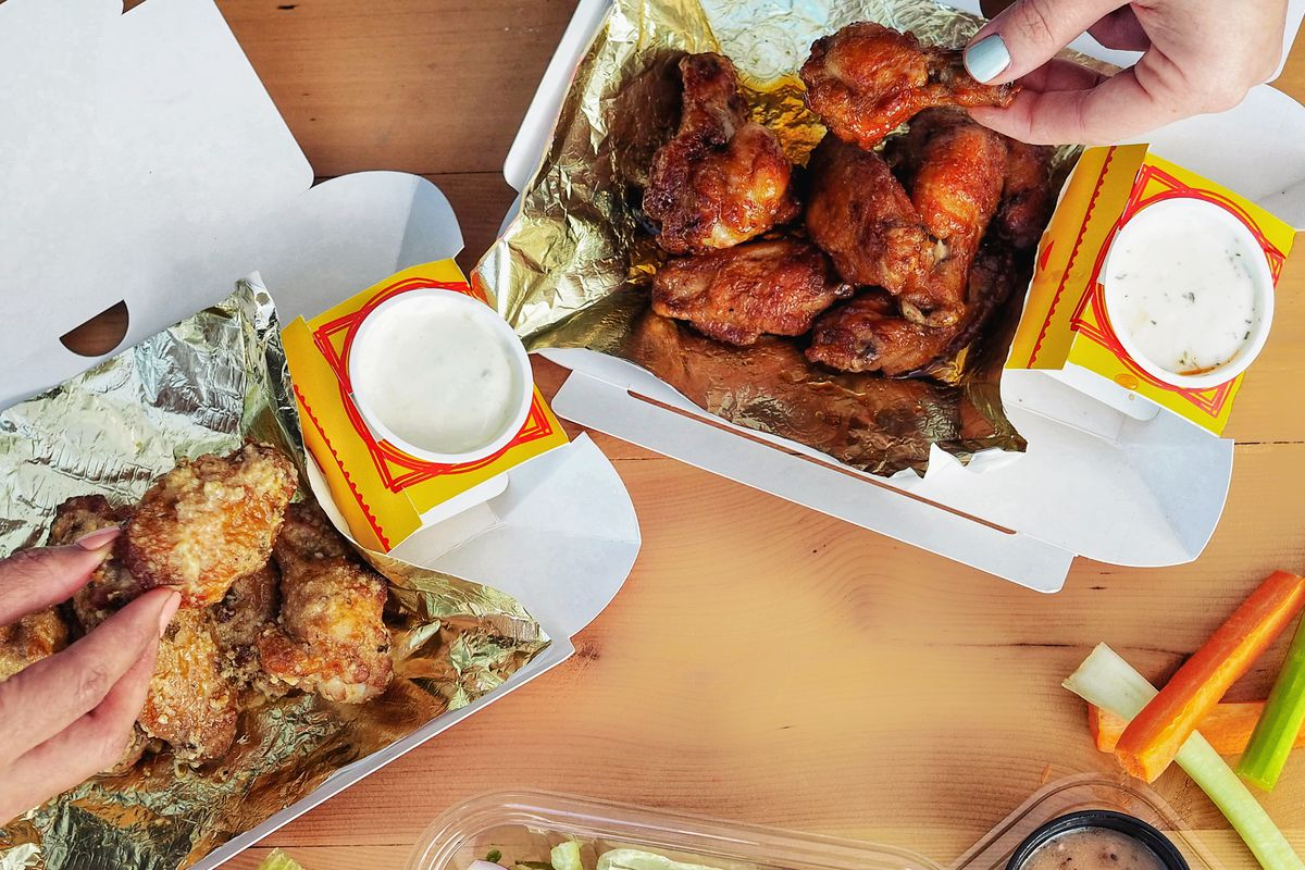 An aerial view of to-go containers, including dipping sauces, salads, and hot wings