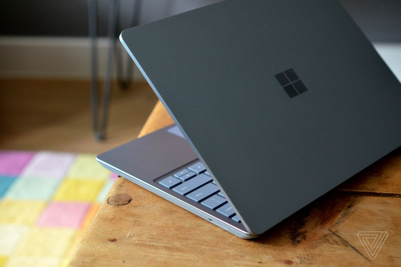 The Surface Laptop Go on the corner of a table half open, seen from the back.