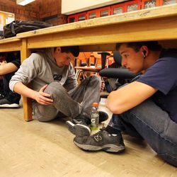 Danny Maltby, right, and Josh Finlinson, Taylorsville High School students in Steve Woolley's physics class, sit under their desks during an earthquake drill as part of The Great Utah ShakeOut, Tuesday, April 17, 2012.