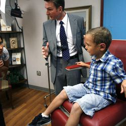 Taisian Beckstead looks at her son, 5-year-old Kamden Gill, after Dr. Steven Mobley removed his bandages at the Surgical Specialty Center in Salt Lake City on Friday, Sept. 23, 2011. Mobley performed an otoplasty to fix Kamden's protruding ears.