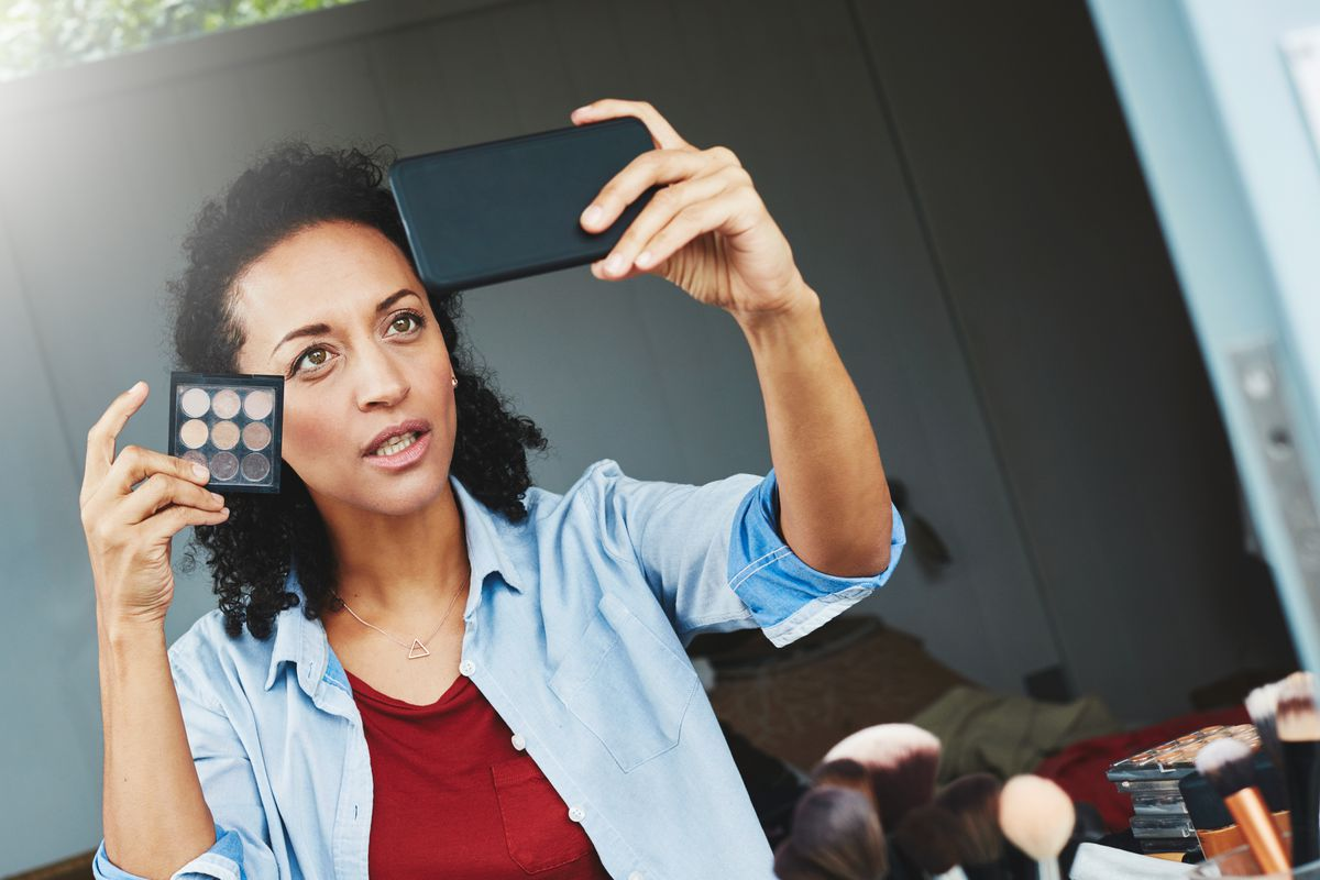 A woman takes a selfie while holding a cosmetic palette up to her face.