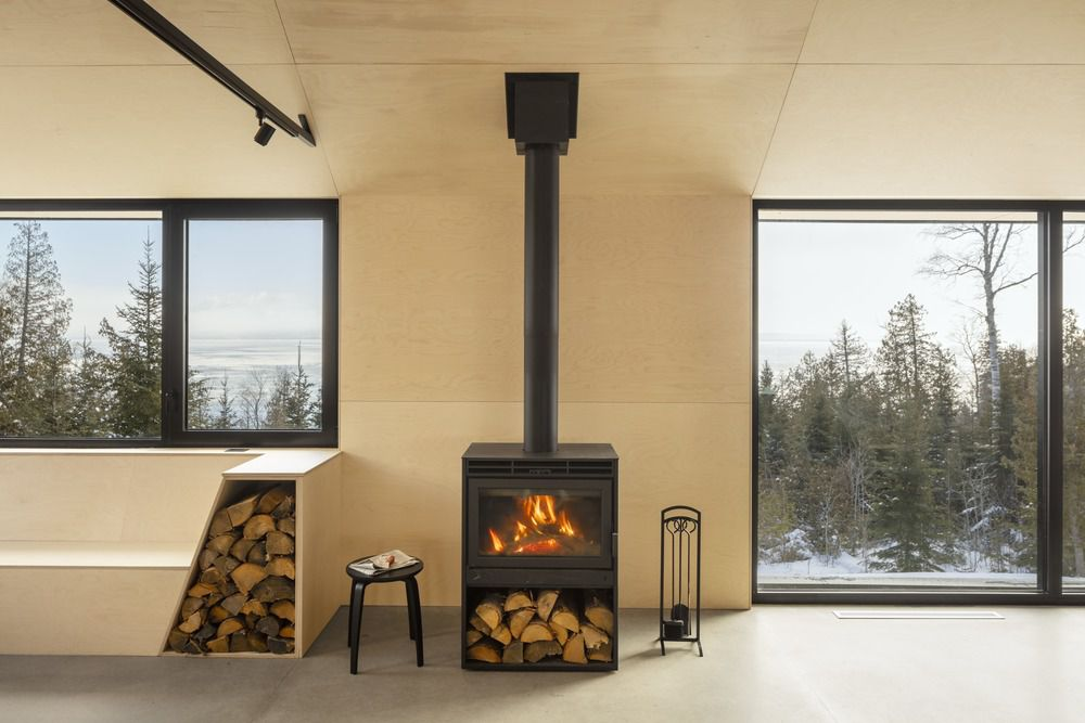 Black wood burning stove in plywood clad living room with large windows.