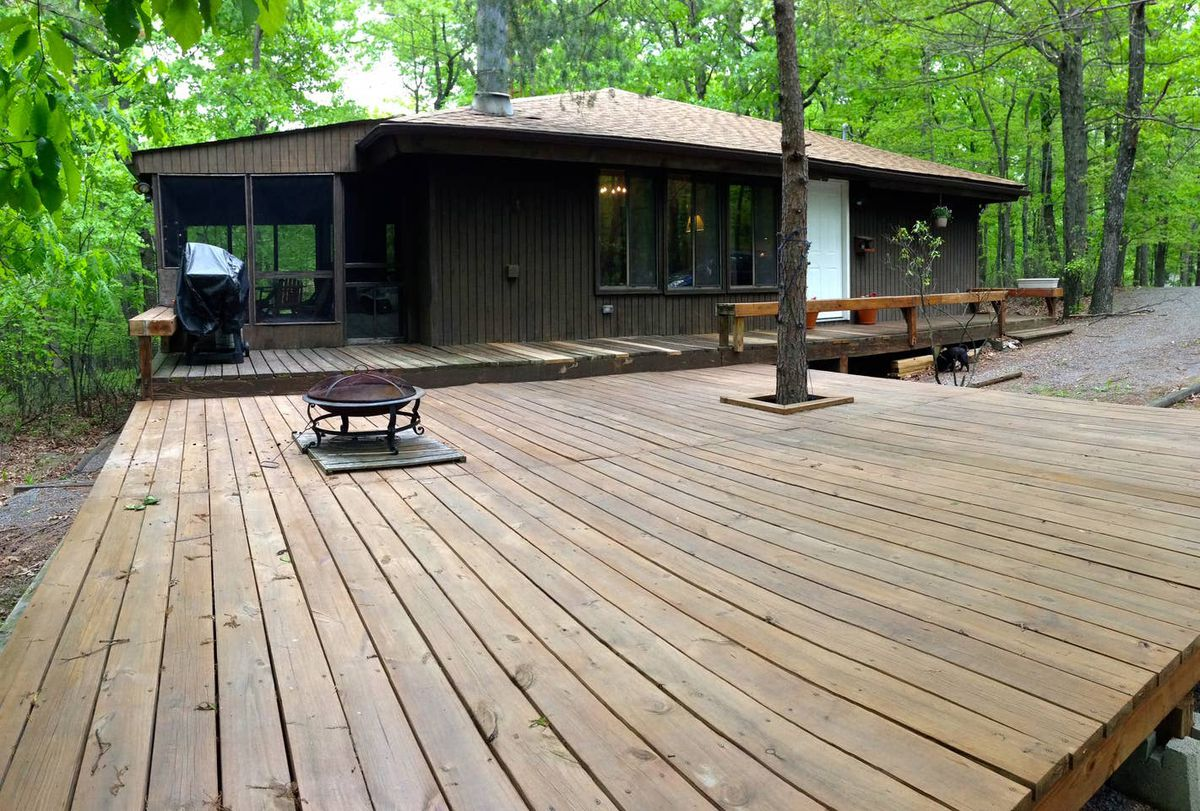 A one-story wood cabin in Hedgesville, West Virginia, with a wide wood deck out front.