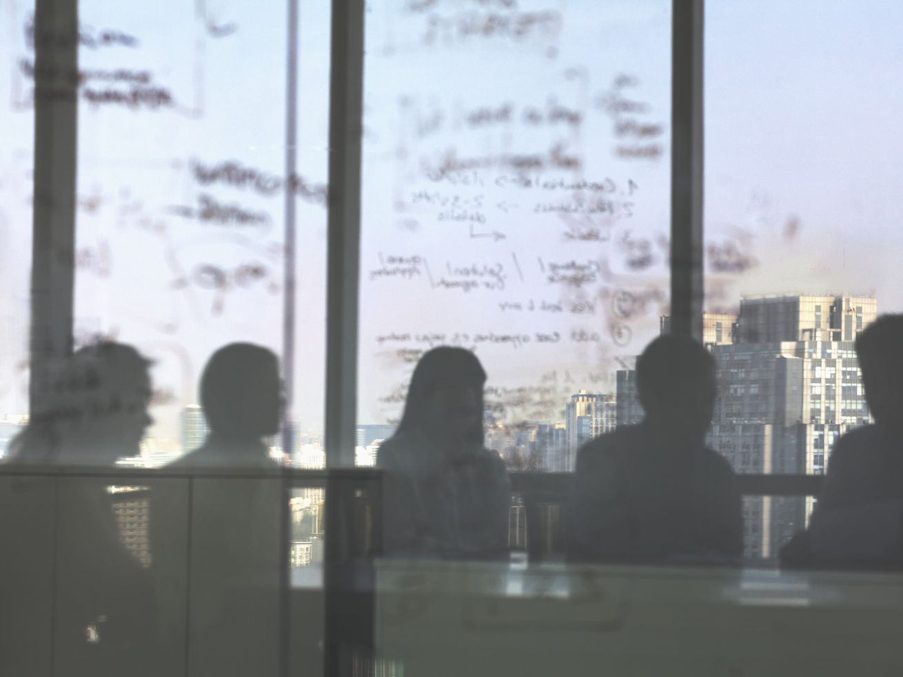Silhouettes of board members and a written-on white board seen through glass.