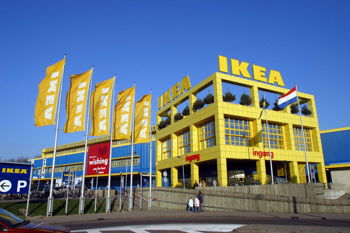 A large Ikea store, with Ikea flags outside.