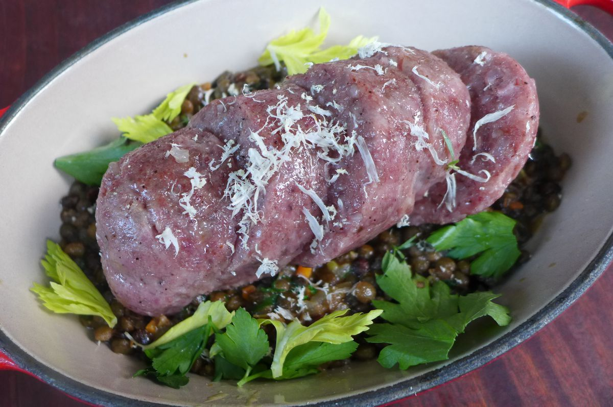 A thick sausage resting on a bed of tiny lentils in an off white oblong bowl.