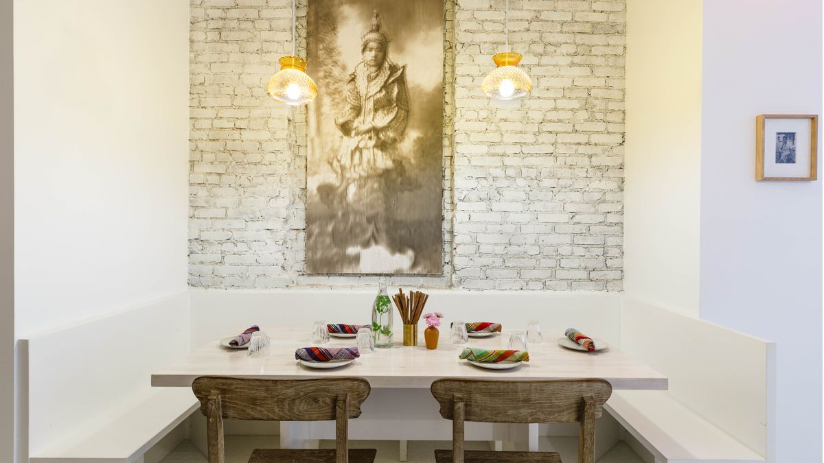 Inside the Burmese Brooklyn restaurant Rangoon with a table seating four in focus with a painting of a woman in the background