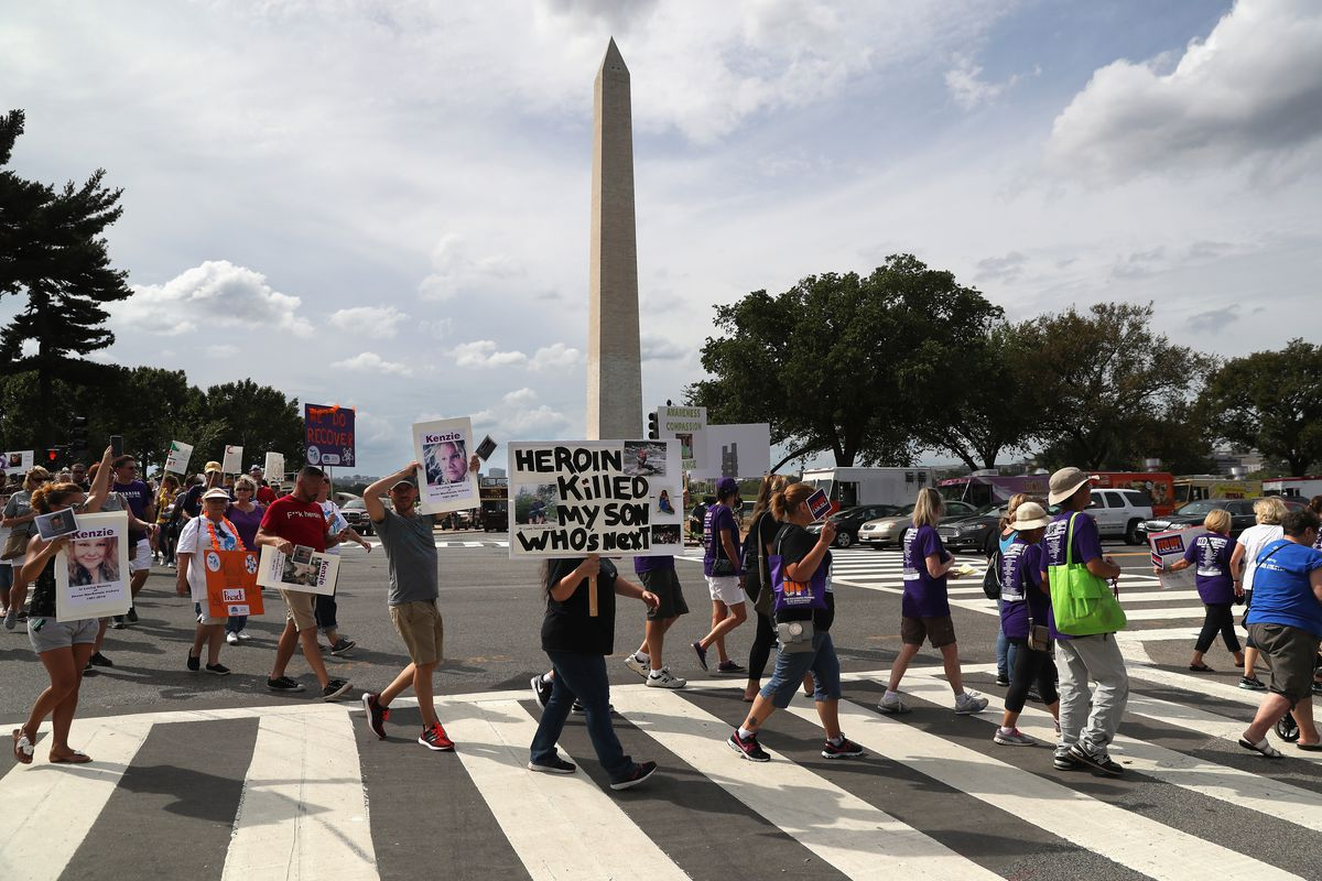 """Activists march in Washington, DC, to call for action against the opioid epidemic. One holds a sign reading, """"Heroin killed my son. Who's next?"""""""