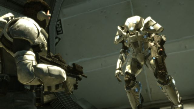 a robot faces down an armed and armored human