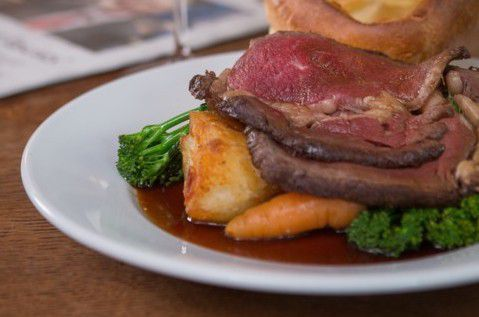 Roast potatoes, carrots, rare beef, and gravy assembled as a Sunday roast on a white plate, on a wooden pub table