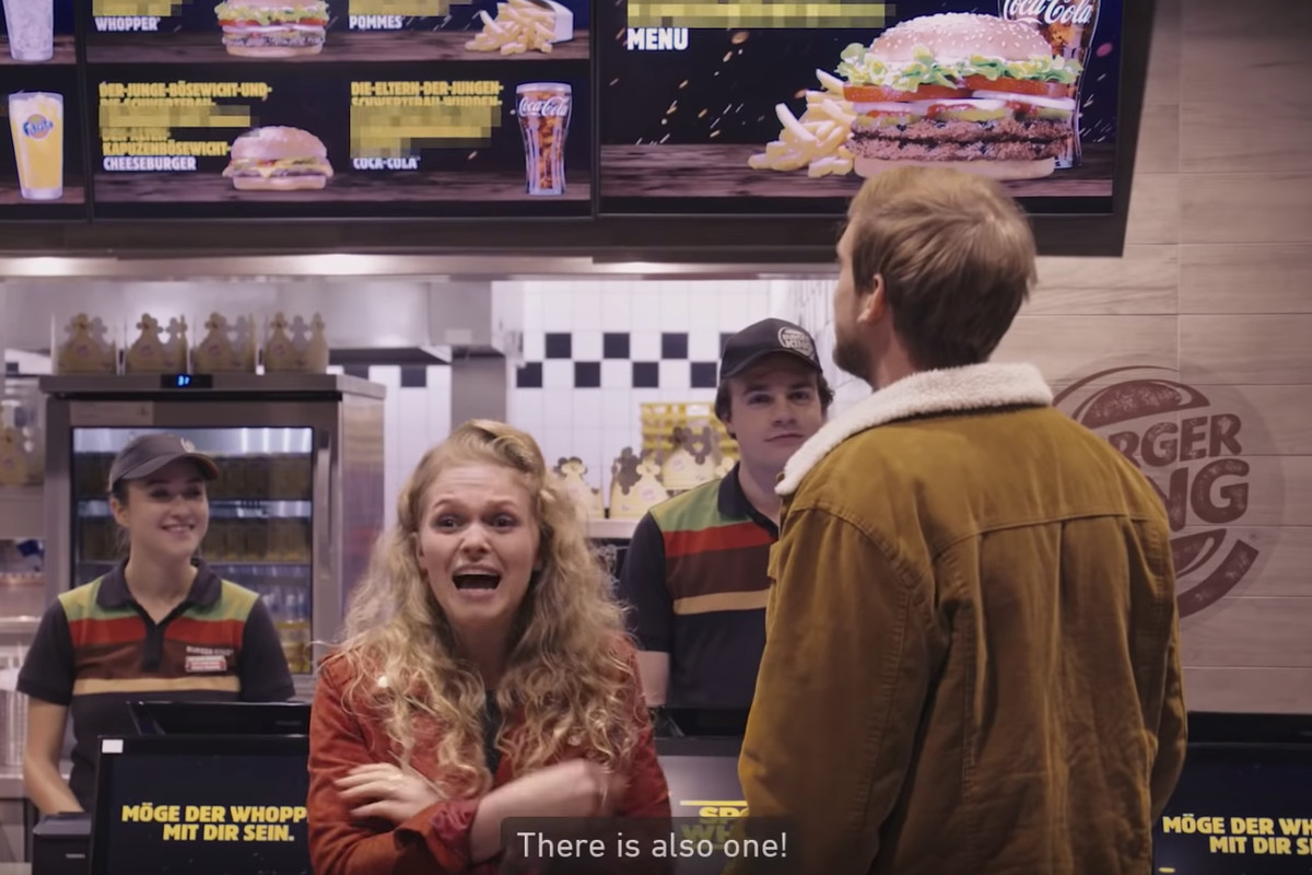A blonde woman with her back turned to a Burger King counter and a shocked look on her face