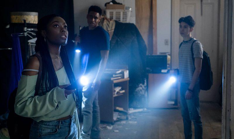 Asjha Cooper, Frabrizio Guido and Mason Beauchamp explore a dark room with flashlights in Black As Night