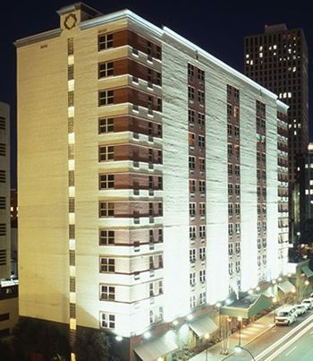 A beige high-rise hotel stands above New Orleans at night.