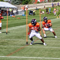 Broncos RB De'Angelo Henderson Sr. (front) and FB Andy Janovich (back) make cuts through the pole course drill.