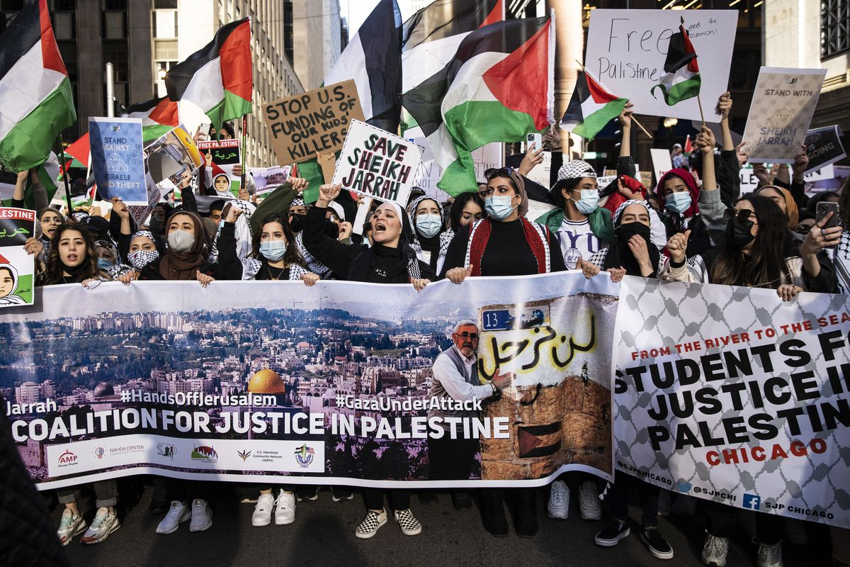 Demonstrators hold up a banner for the Coalition for Justice in Palestine during a march through the Loop, May 12, 2021. The coalition is an umbrella organization for a number of Chicago-chapter pro-Palestine groups.