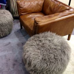 Oversized leather chairs and poufs.